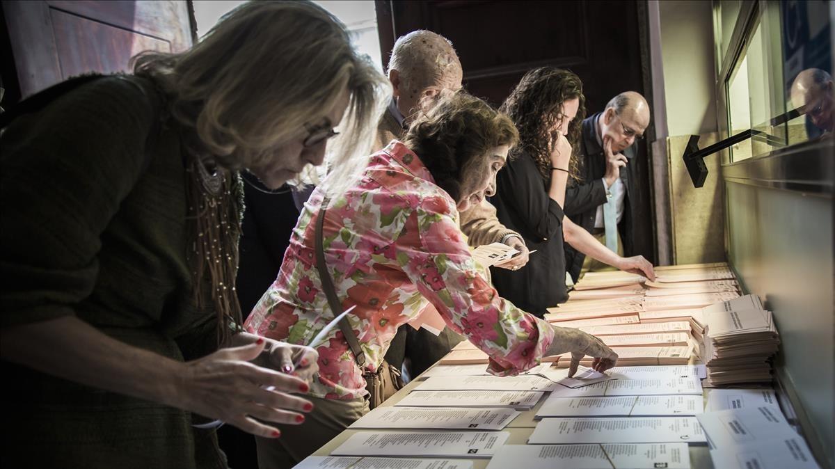 Un grupo de electores revisa papeletas en unas elecciones.