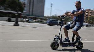 Un hombre circula por Barcelona en un patinete eléctrico de grandes dimensiones.