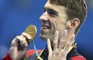 Phelps muestra su medalla señalando los cuatro oros que ha conseguido hasta ahora