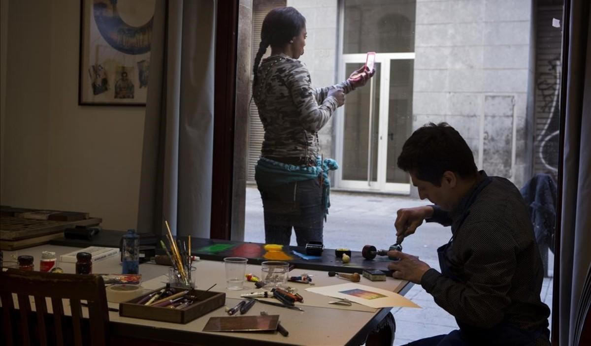El artista Edgar Márquez trabaja tras los ventanales del taller Art Resident, en el número 37 de Robador, mientras fuera, en la calle, una chica aguarda clientela.
