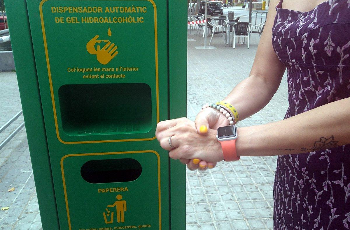 Ciudadano usando el dispensador de gel hidroalcohólico en la vía pública de Sabadell