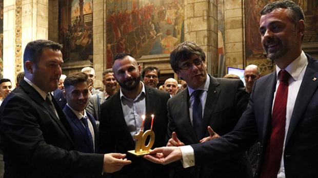 >El 'president', Carles Puigdemont, y el 'conseller' de Empresa i Coneixement, Santi Vila, este martes, 1 de agosto, en la recepción en la Generalitat a los organizadores del Circuit Festival, con una tarta de aniversario.
