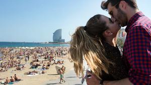 SOLSTICIO DE VERANO. Una pareja se besa junto a la playa, en Barcelona.