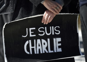 Una mujer sostiene un cartel de apoyo a la revista 'Charlie Hebdo' durante uno de los múltiples homenajes que se celebraron por todo el mundo al día siguiente del atentado en París del pasado día 7.