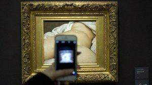 Un visitante toma una foto al cuadro 'El origen del mundo' de Gustave Courbet en el Museo d'Orsay de París.