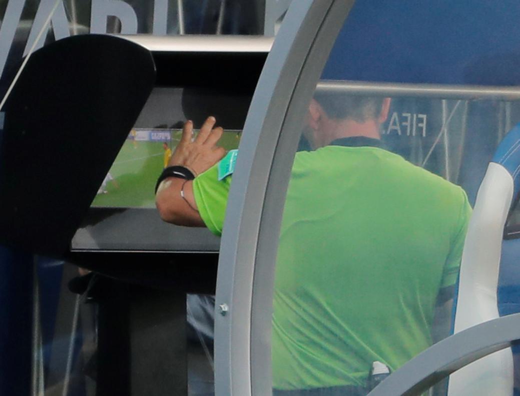 El arbitro revisa por televisión la jugada que no señaló en el campo y que corrigió para dictaminar penalti contra Corea.