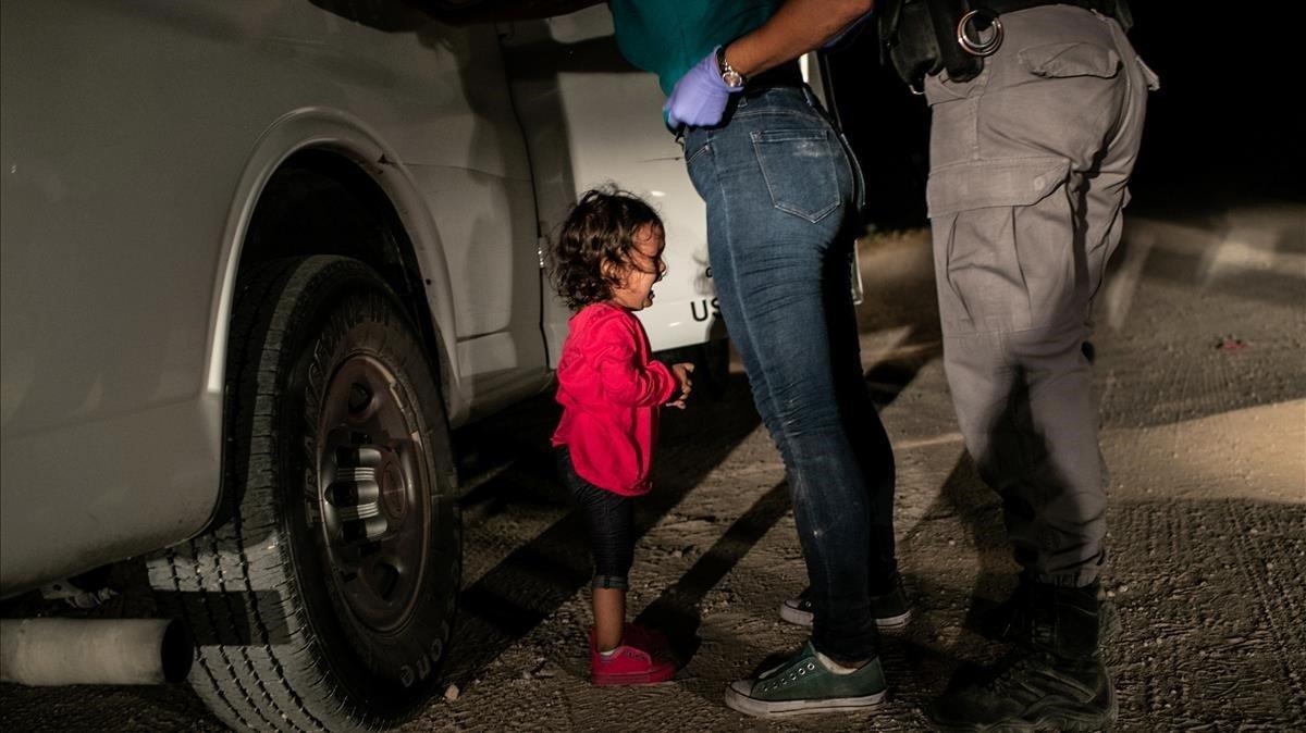 Convertida en icono del drama migratorio, una niña hondureña llora ante su madre detenida en la frontera de EEUU.