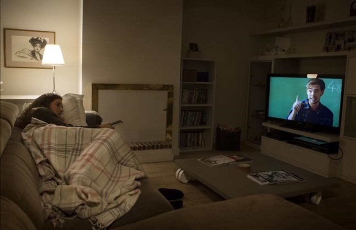 Una joven ve la tele en prime time.