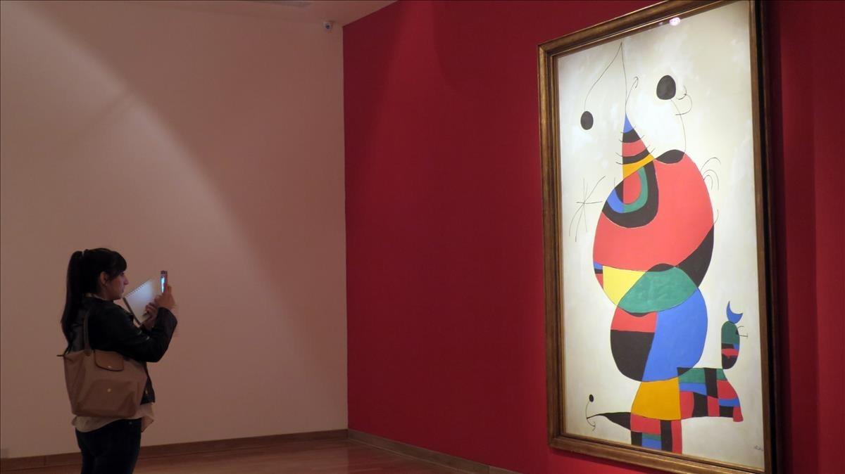 Una visitante observa Mujer, pájaro, estrella (Homenaje a Pablo Picasso), un óleo de 1973.