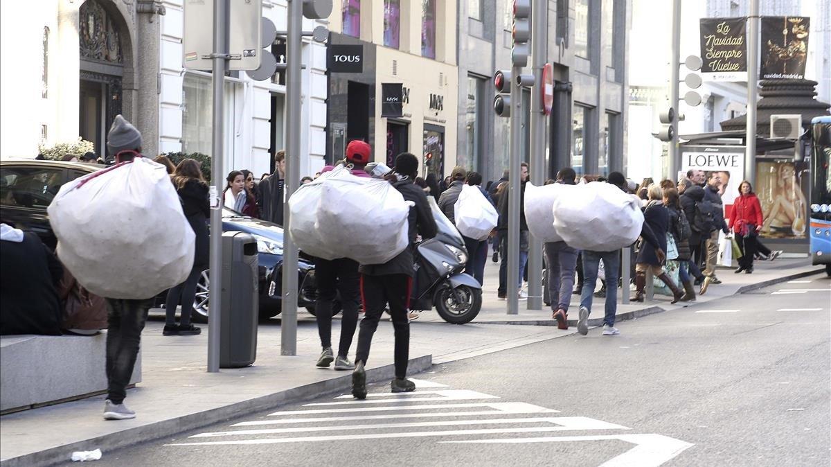 Manteros caminan con sus fardos a cuestas por la Gran Via de Madrid, tras no poder desplegar las mantas.