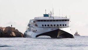 El 'ferry' de Baleària, encallado en una escollera del puerto de Dénia.