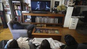 Una familia ve la película 'El hoyo' desde el salón de casa.