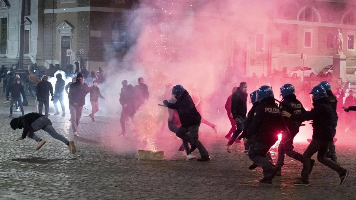 La policía antidisturbios ymiembros deextrema derecha se enfrentan durante una protesta contra el toque de queda por coronavirus.