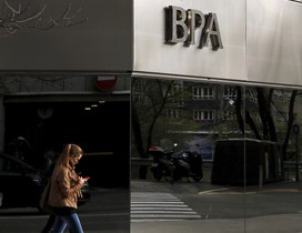 A woman looks at her mobile phone as she walks past a BPA office in Andorra la Vella