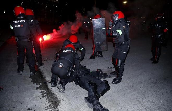 Agentes de la Ertzaintza atienden a su compañero mherido antes del partido entre el Athletic y el Spartak