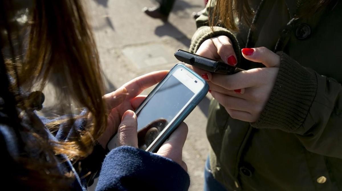 Adolescentes con un móvil en una imagen de archivo