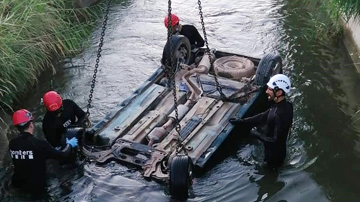 Los Bomberos sacan el coche que ha caido dentro el Canal d'Urgell en Puigverd.
