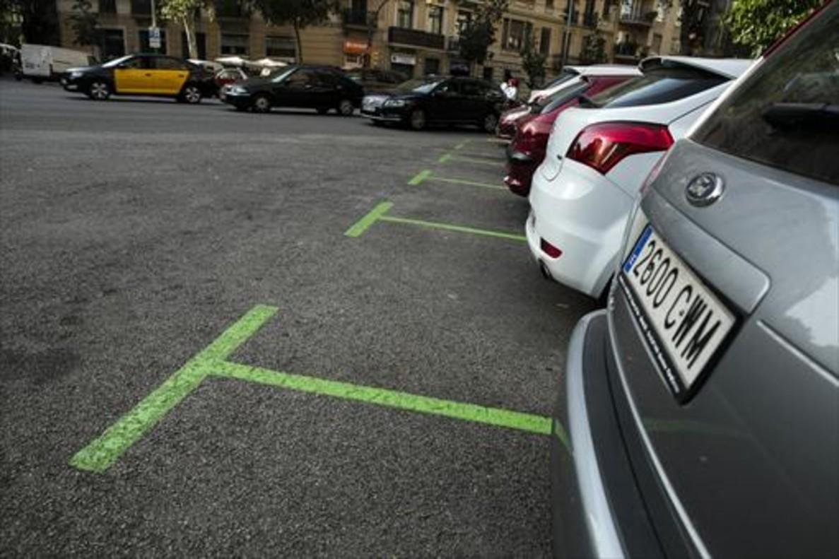 Coches estacionados en plazas de zona verde en el Eixample.