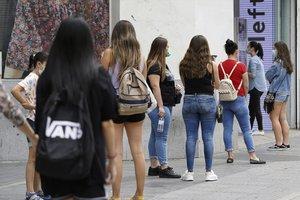 Colas a la entrada de una tienda de ropa en la Gran Vía de Madrid para cumplir las normas de higiene como consecuencia de la pandemia por COVID-19 .
