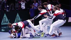 El equipo francés se abalanza sobre Lucas Pouille tras conseguir el punto definitivo sobre Steve Darcis en la final de la Copa Davis.