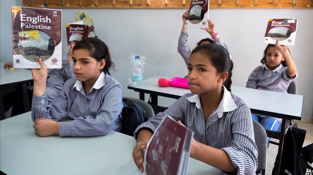 Estudiantes de sexto curso asisten a una clase de inglés en la escuela para niñas de la agencia de la ONU para los refugiados palestinos UNRWA en un campo de refugiados en Shuafat,al norte de Jerusalén.
