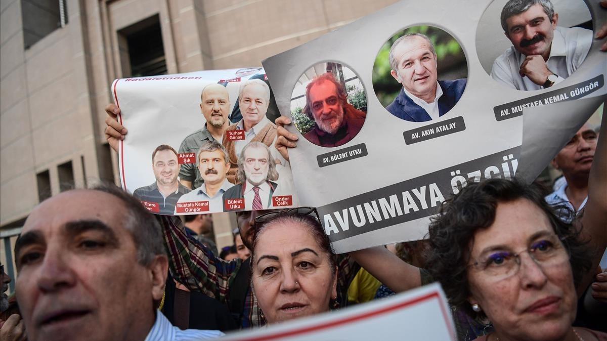 Un grupo de manifestantes muestran imágenes de periodistas del diario opositor 'Cumhuriyet', en una protesta en Estambul, el 28 de julio.