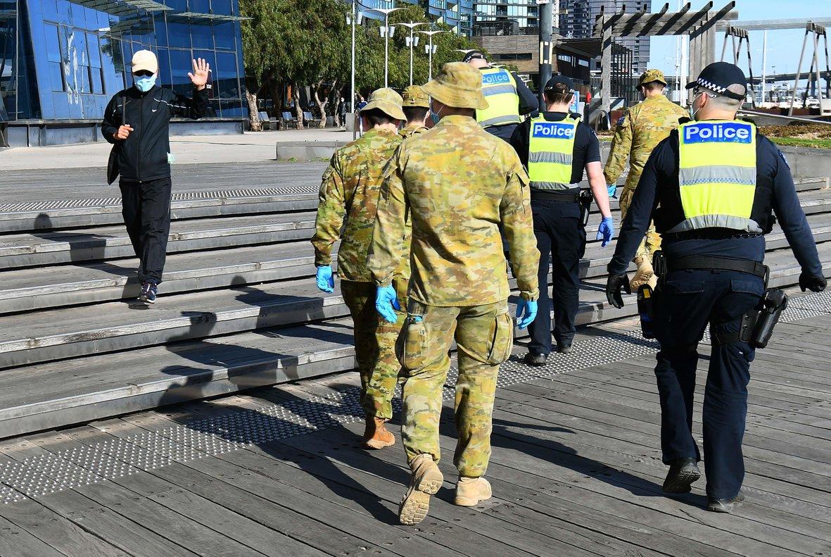 Un hombre saluda a un grupo de soldados y policías tras decretarse el toque de queda nocturno en Melbourne por covid-19.
