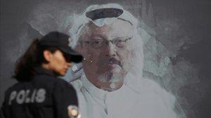 Una policía turca pasa frente una fotografía de JamalKhashoggi en el acto en recuerdo del periodista asesinado celebrado en Estambul.