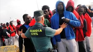 Un agente de la Guardia Civil organiza una fila de inmigrantes llegados en patera, en Algeciras, en una imagen de archivo.