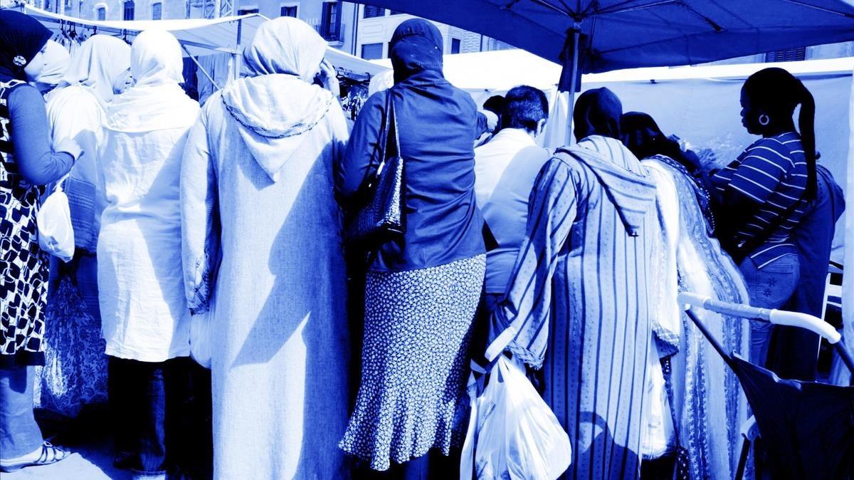 Mujeres comprando en un mercado ambulante.