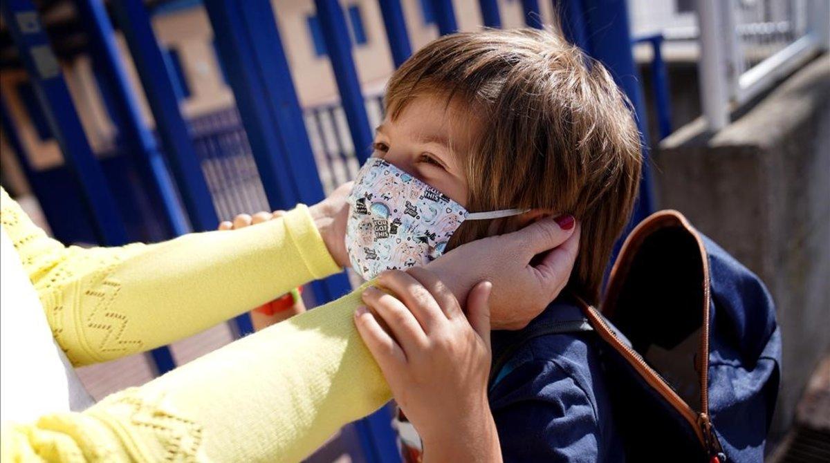 Una madre pone a su hijo una mascarilla a las puertas de un colegio en Moralzarzal (Madrid).