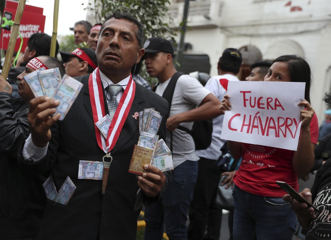 A protester dressed as a judge shows a miniature copy of Peru s constitution and fake money  next to a woman holding a sign that reads in Spanish  Chavarry Get Out   referring to Peru s attorney general Pedro Chavarry  at San Martin Plaza in Lima  Peru. AP Photo Martin Mejia