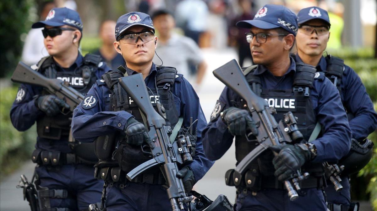 Miembros de la policía de Singapur patrullan los alrededores del hotel St. Regis donde se hospeda el líder norcoreano Kim Jong-un en Singapur .