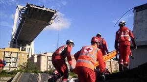 Trabajadores de la Cruz Roja de Italia buscan desaparecidos entre los escombros del puente Morandi en Genova.