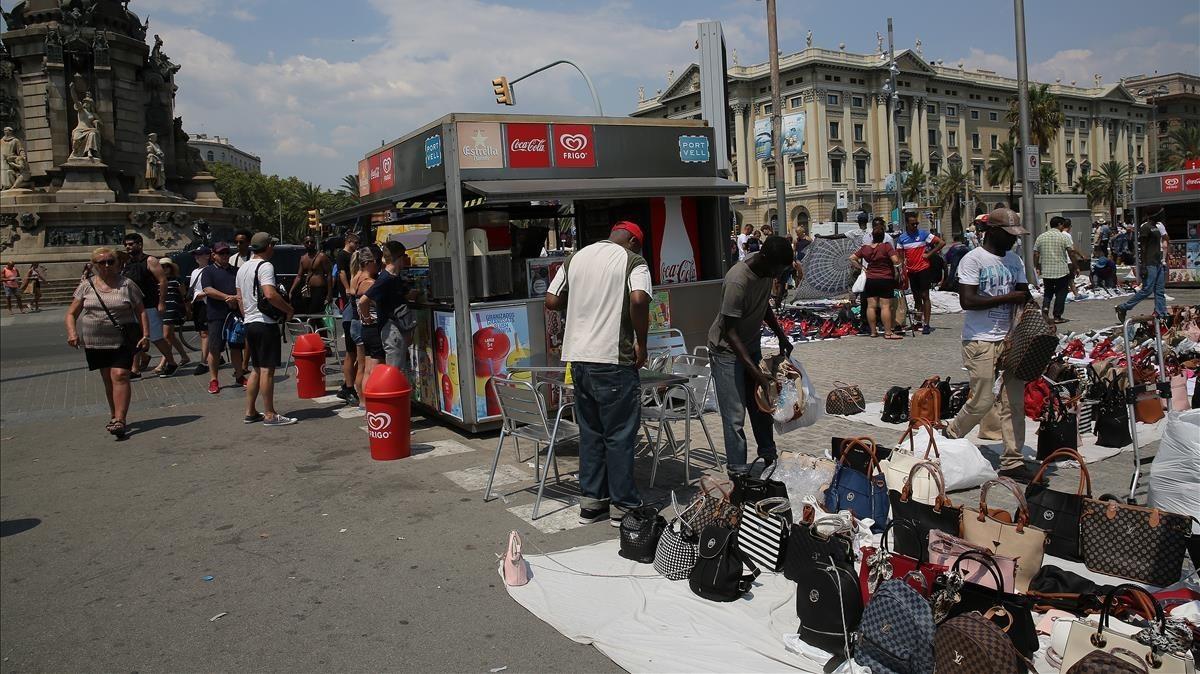 Quiosco de helados y bebidas en el Portal de la Pau, rodeado de vendedores.