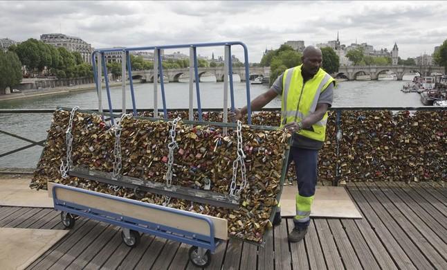 Un operario trabaja en la retirada de los candados de las barandillas del puente de las Artes, en París.