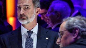 El rey Felipe VI mira de reojo al president, Quim Torra, en la cena del Mobile World Congress, este domingo.