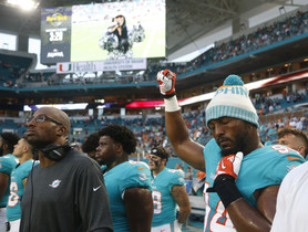 Miami Dolphins defensive end Robert Quinn (94) raises his right fist during the singing of the national anthem, before the teams NFL preseason football game against the Tampa Bay Buccaneers, Thursday, Aug. 9, 2018, in Miami Gardens, Fla. (AP Photo/Wilfredo Lee)