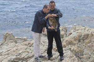 Romain Fornell, que besuquea a un pescado, y José Pulido, en las rocas de SAgaró. Foto: Glòria Sánchez / Iconna