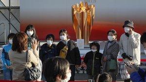 Ciudadanos japoneses se fotografian ante la antorcha olímpica debidamente protegidos.