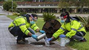 Técnicos recogen una muestra de aguas residuales para rastrear el COVID-19 en València
