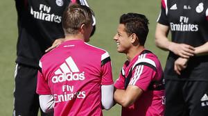 Toni Kroos y Chicharito bromean durante el entrenamiento de este martes en la ciudad deportiva de Valdebebas.