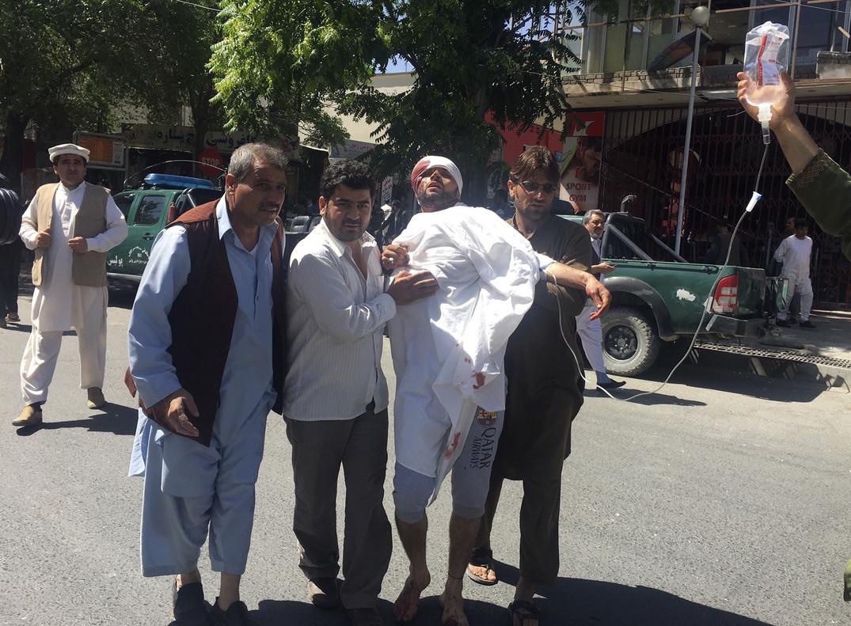 Tres personas ayudan a un hombre herido en el atentado de este miércoles en Kabul.