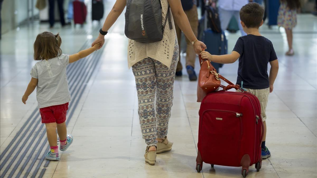 Una mujer acompañada de dos pequeños arrastra una maleta en la estación de Sants, el viernes pasado.