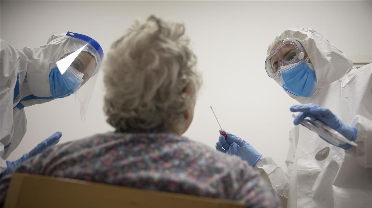Enfermeras de atención primaria realizan un test PCR a una mujer en Barcelona, el pasado mayo.