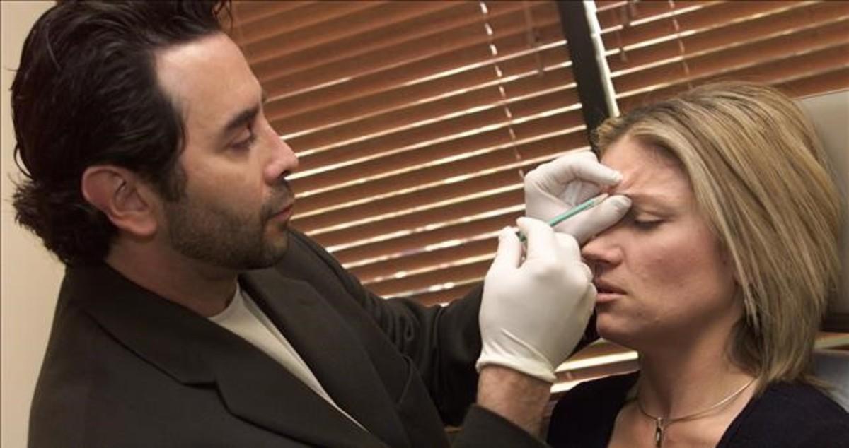 Un especialista en medicina plástica aplica a una paciente un tratamiento de bótox.