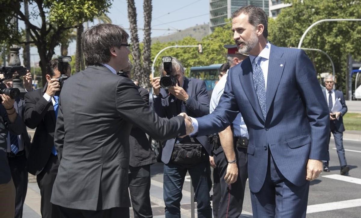 Carles Puigdemont y el rey Felipe VI se saludan al llegar a la ceremonia de entrega de las becas de La Caixa.