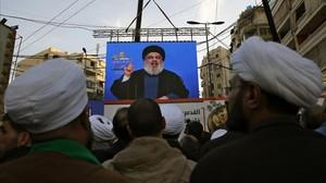 Seguidores de Hizbulá escuchan a su líder que aparece en una pantalla gigante en una manifestación en Beirut.