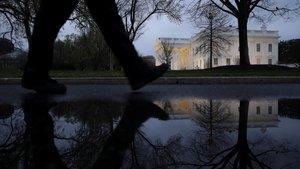 Un peatón camina por la entrada del ala oeste de la Casa Blanca, en Washington., donde se ha iniciado la cuarentena.