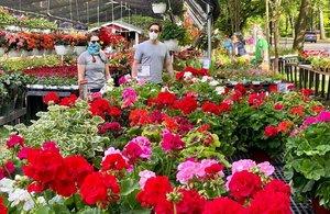Personas protegidas con mascarillas, mientras compran flores en Washington.